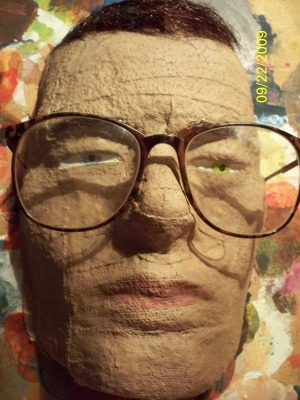 a papier mache face with glasses